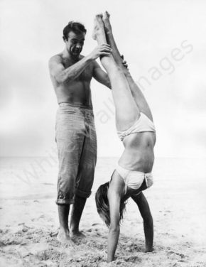 Sean Connery helping a lady with her daily handstand.  He knows the heir-achy.
