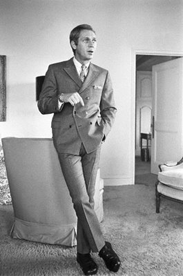 Steve McQueen expertly goes for the cross legged lean while nonchalantly showing off his double breasted suit.