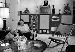 Sinatra relaxes at his home in Palm Springs. Notice the state-of-the-art technology and the bowl of either cigarette packs or wads of money on the table. A true gentleman.