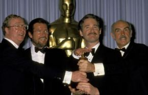 Michael Caine, Roger Moore, Kevin Klein and Sean Connery win an award for best tuxedo baton relay.  The award they won is behind them.
